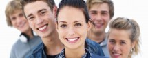 Closeup of young smiling friends standing in a row with woman in